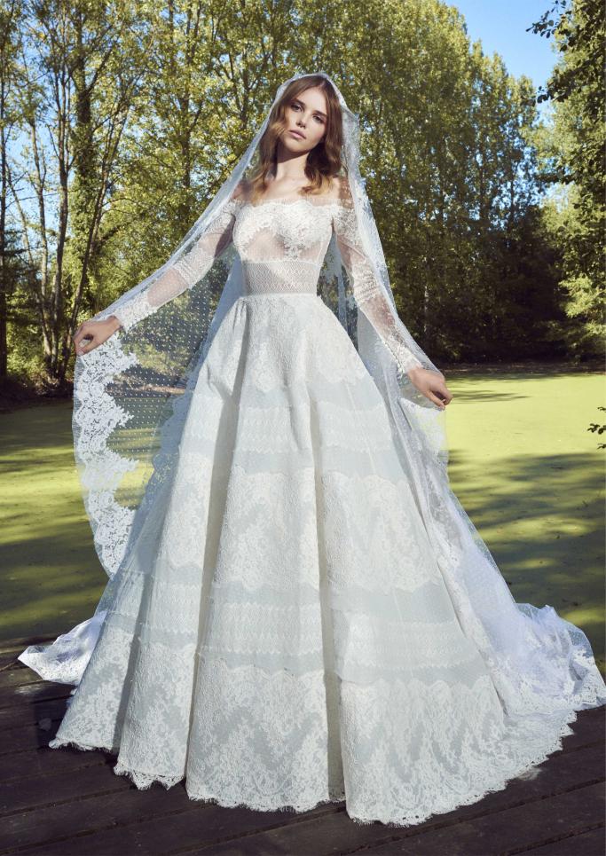 78693b30e لفتتنا فساتين زفاف زهير مراد للمحجبات، حيث التصاميم المحتشمة بالأكمام  الطويلة الشفافة، والمزينة أيضاً بالورود.